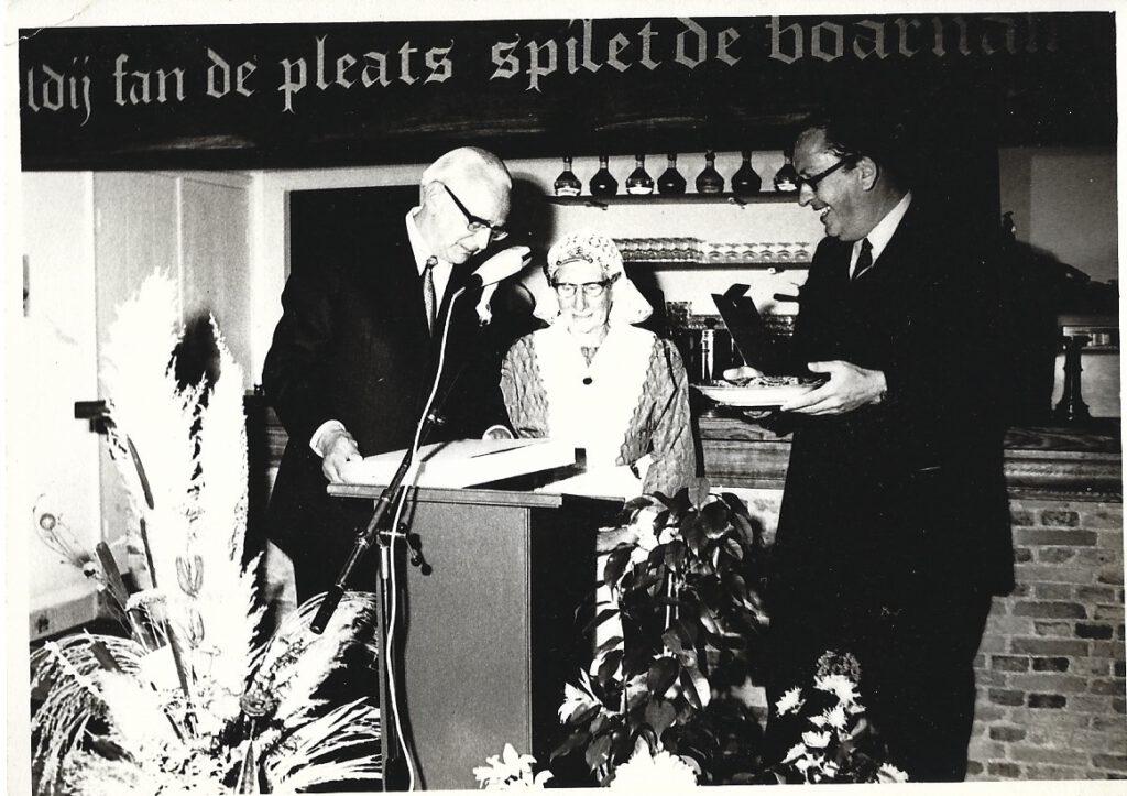Commissaris van de Koning Hedzer Rijpstra en Burgemeester Atze Oosterhoff bieden Nynke Postma een Makkummer bord aan bij de opening van het restaurant, 15 juni 1972